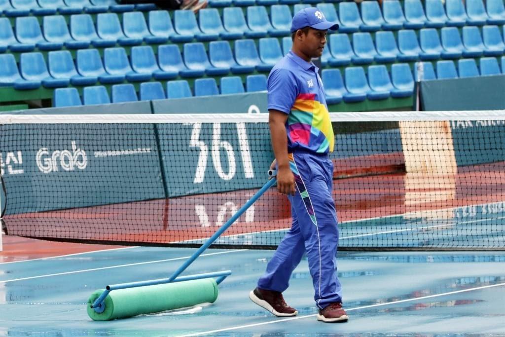 Petugas mengeringkan lapangan yang sempat diguyur hujan saat pertandingan babak semifinal ganda campuran, Asian Games 2018 di JSC Tennis Courts, Palembang, Sumatera Selatan, Jumat(24/8). ANTARA FOTO/INASGOC/Hendra Syamhari/nym/18
